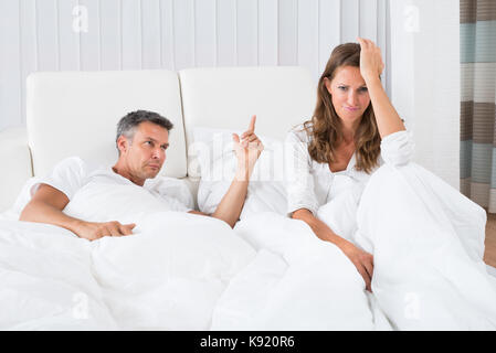 Man Arguing With Depressed Woman Sitting On Bed - Stock Photo
