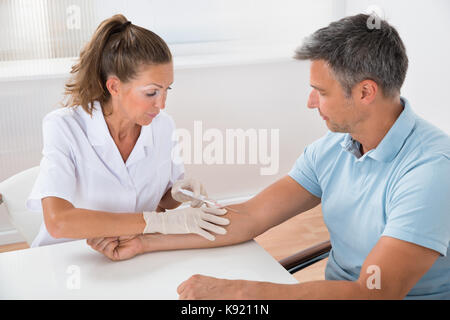 Portrait Of Doctor Drawing Blood  From Patient With Syringe In Hospital - Stock Photo