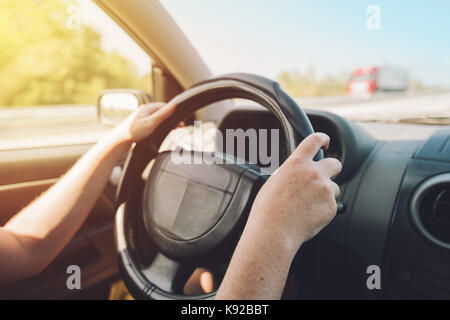 Female hands holding on black steering wheel and driving car on motorway on sunny summer day - Stock Photo