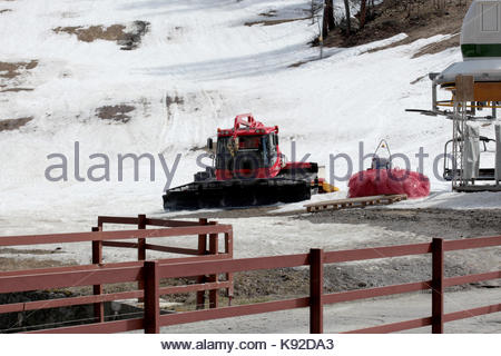 closed ski chairlift and a parked snowcat at the end of skiing season - Stock Photo