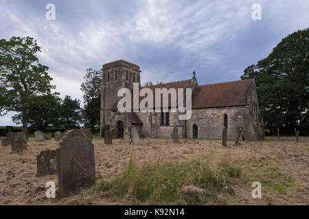 Summer evening view by headstones in the churchyard, of the exterior of historic All Saints' Church, Moor Monkton, - Stock Photo