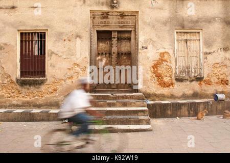 A man cycling past a traditional Swahili door, Stone Town, Zanzibar, Tanzania, East Africa - Stock Photo