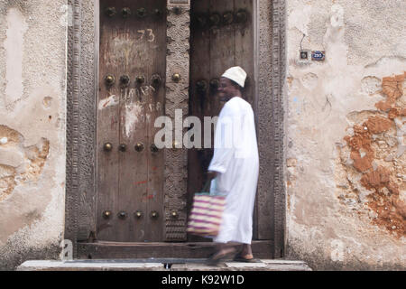A man in traditional dress walking though an ornate carved wood door, Stone Town, Zanzibar, Tanzania, East Africa - Stock Photo