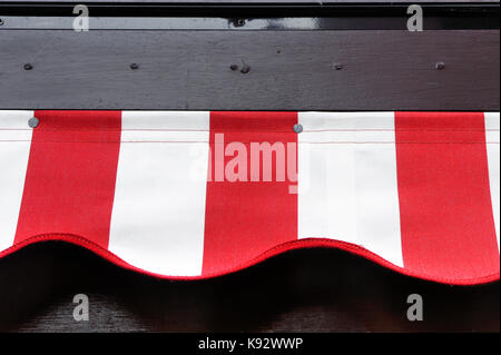 Part of a red and white canvas canopy outside a cafe - Stock Photo