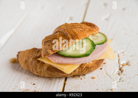 Croissant with ham, cheese and cucumber - Stock Photo