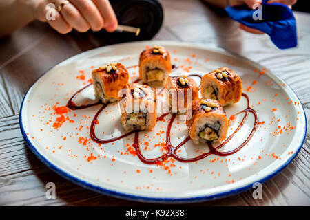 Adding pine nuts to sushi roll close up - Stock Photo