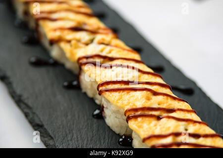 Freshly cooked uncut sushi roll on black board - Stock Photo
