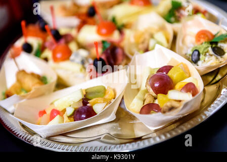 Home made canapes small sandwiches appetizers. Mix of different finger food snacks for a party or banquet on a plate. - Stock Photo