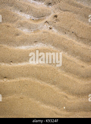 Natural wave pattern in sand on a beach texture. Graphic element of naturally created sand waves on a beach, created - Stock Photo