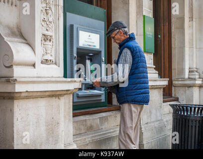 Old / elderly man withdrawing sterling pounds / British money from cash machine (ATM) outside bank in Stamford town - Stock Photo