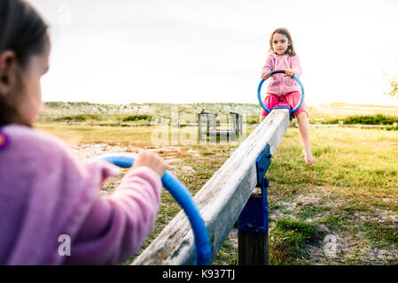 Little twin girls children are riding seesaw swing in park. Active children playing on teeter-tooter n a playground - Stock Photo