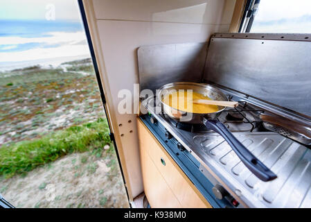 Cooking dinner or breakfast in camper RV with beach view. Preparing eggs with magnificant view of Nemiña beach Galicia - Stock Photo