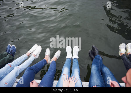 Young people friends sitting on the river bridge, lifestyle, feet over blue water - Stock Photo