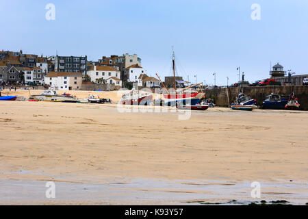 Fishing and pleasure boats beached on the strand at St Ives, Cornwall, at low tide - Stock Photo