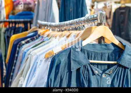 Rail of second-hand clothes on display at Old Spitalfields Market in London - Stock Photo