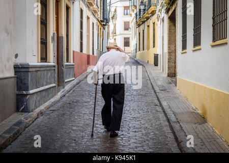 Rear view of elderly man with cane walking along cobbled street in Sevilla, Andalusia, Spain. - Stock Photo