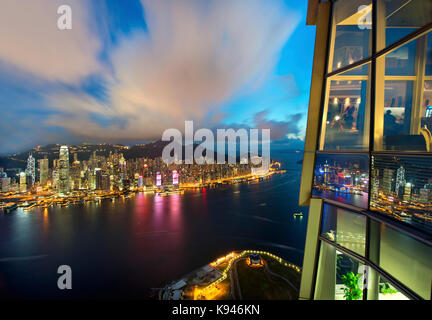 Aerial view of Hong Kong cityscape with illuminated skyscrapers at dusk. - Stock Photo
