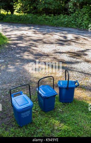 Blue plastic food waste bins awaiting collection on a narrow country road in Monmouthshire, Wales. - Stock Photo