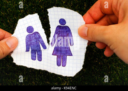 Woman hands ripping piece of paper with hand drawn man and woman figures. Grass background. Doodle style. - Stock Photo
