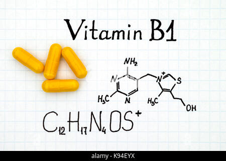 Chemical formula of Vitamin B1 and some yellow pills. - Stock Photo