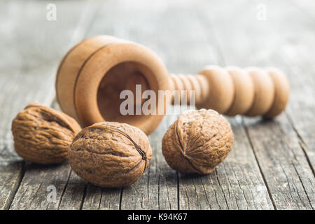 Dried walnuts and nutcracker on wooden table. - Stock Photo