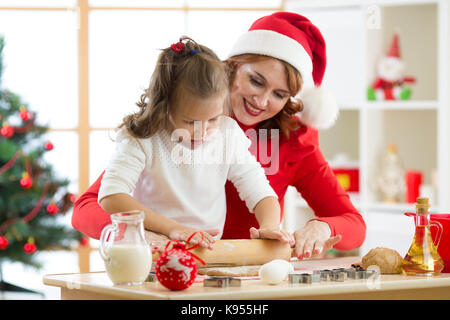 family mother and child rolling the dough, bake christmas cookies in festival decorated room - Stock Photo