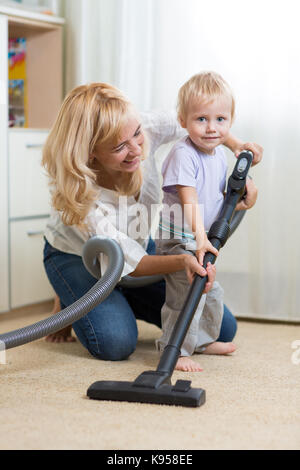 happy family cleans the room with hoover - Stock Photo