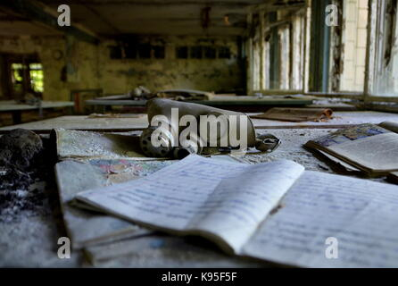 A gas mask a some notebooks in an abandoned school in the town of Pripyat, evacuated after the Chernobyl disaster, - Stock Photo