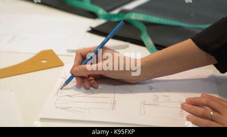 Tailor.Hands notch tailor tailor's scissors cloth. Female tailor stitching material at workplace. Preparing fabric - Stock Photo