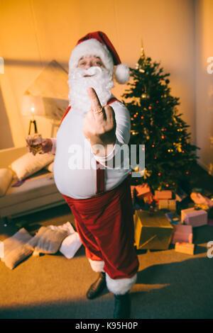 bad santa showing middle finger - Stock Photo