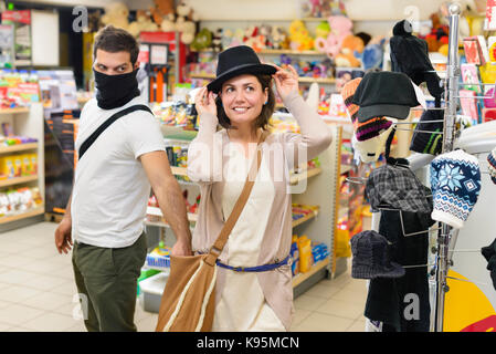 Thief stealing from handbag of a woman trying a hat  in a store - Stock Photo