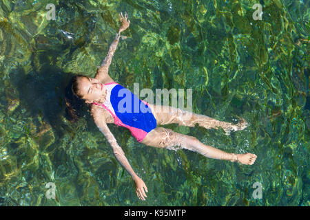 Floating on her back at sea, summer day - Stock Photo