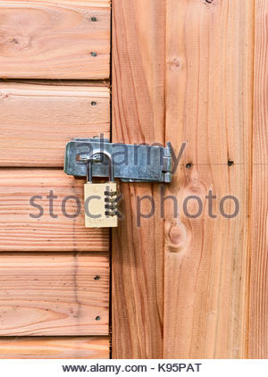 A combination padlock on a shed wooden door for security - Stock Photo