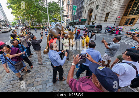 The Charging Bull Statue and the Fearless Girl Statue surrounded by tourists in the Financial District, near the - Stock Photo