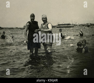 Antique c1920 photograph, two women in period swimming suits at a popular bathing lake, with boats in the background. - Stock Photo