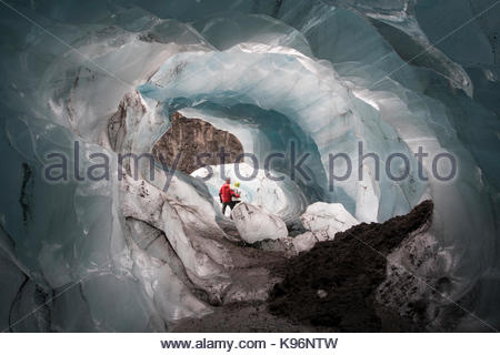 A couple poses in a natural ice cave that formed under Svinafellsjokull in the Vatnajokull National Park. - Stock Photo