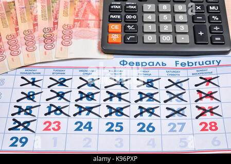 Electronic calculator and banknotes of five thousand rubles are on the calendar with a holiday on February 23. Business - Stock Photo