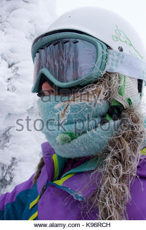 A teenage girl, with frosted hair from skiing in a cold fog, in the Grand Targhee mountains. - Stock Photo