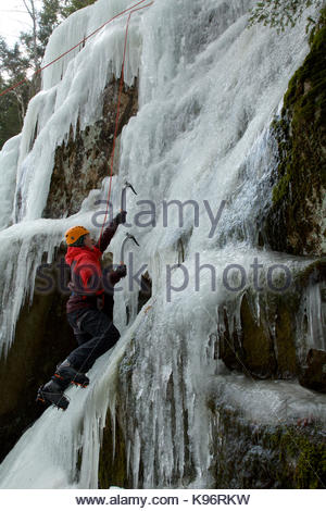 A teen boy ice climbing using ice axes and crampons. - Stock Photo
