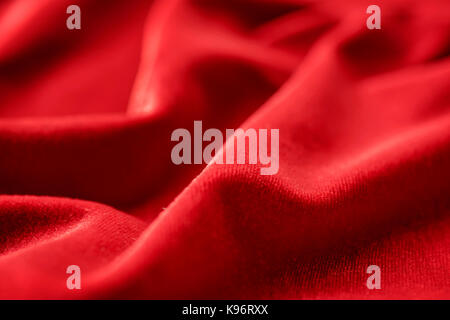 Red silk velvet close up with selective focus. Abstract defocused background - Stock Photo