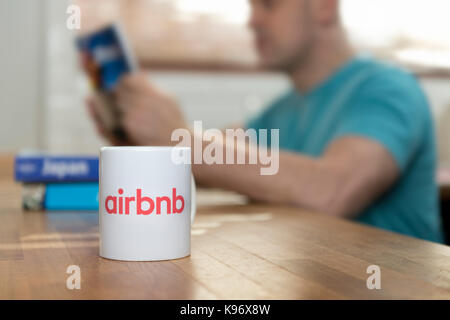A man reads travel guide books in a flat he has rented using the Airbnb app, and a branded Airbnb mug sits in the - Stock Photo