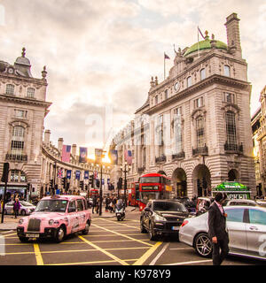 Pink Taxi navigates around Picadilly Circus with Regent Street behind - Stock Photo