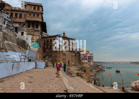 VARANASI, INDIA - MARCH 13, 2016: Wide angle picture of indian men walking in front of Ganges River in the city - Stock Photo