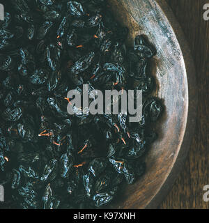 Black dried raisins in plate over wooden background, square crop - Stock Photo