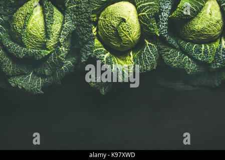 Raw fresh uncooked green cabbage over dark background, top view - Stock Photo