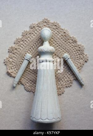 An old fashioned wooden female doll with detached arms, against an old doily. - Stock Photo