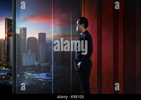 Young businessman looking out the city in the office . evening scene. . - Stock Photo