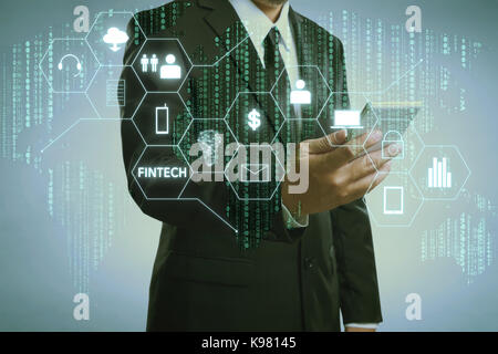 Businessman with fintech icon and internet of things with matrix code background , Investment and financial internet - Stock Photo