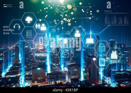 'Fintech' word on digital virtual screen with futuristic city skyline. Hi-tech business concept . - Stock Photo