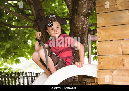 Cute boy in pirate costume sitting on slide in playground - Stock Photo